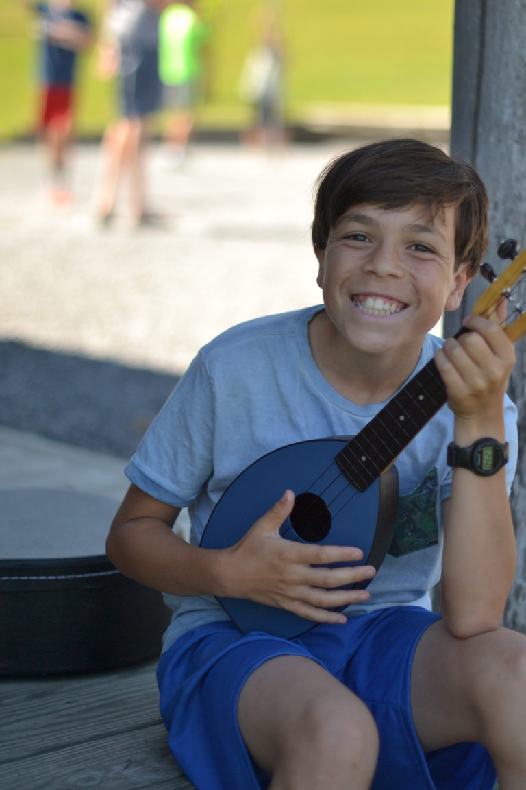 boy smiling and playing ukelele