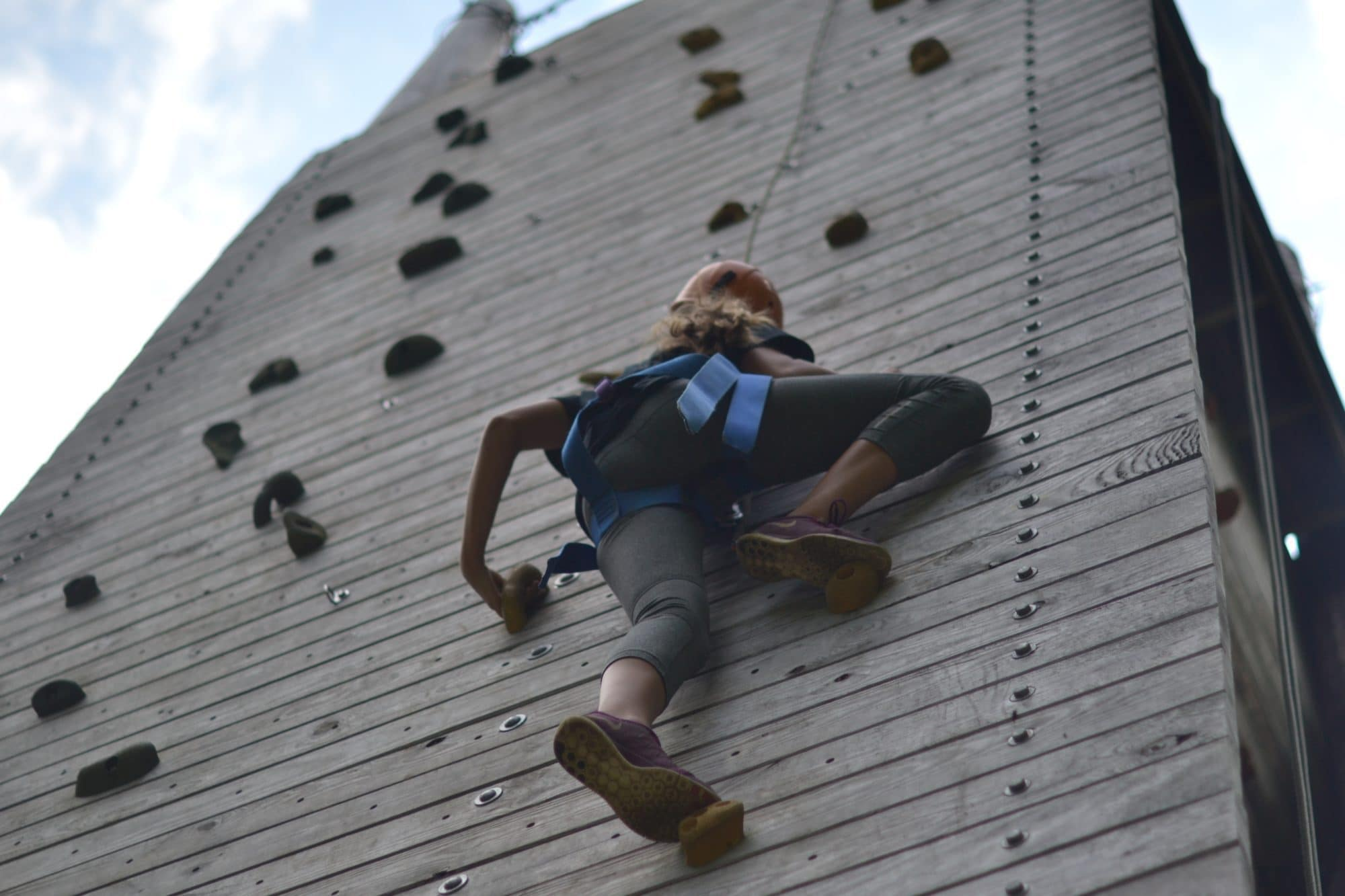 view from the ground of girl scaling the climbing wall